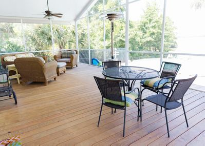 Amazing screened in porch complete with sitting area and dining table