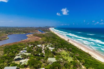 Looking north along Tallow Beach to Cape Byron Lighthouse and Byron township