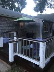 large back deck with patio set and gas grille