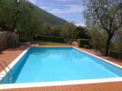 Photo for Wonderful balcony on the lake with beautiful pool and garden between palm and olive trees