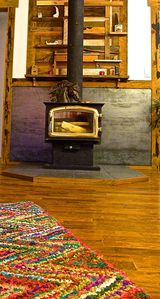 Wood stove features a handcrafted reclaimed wood mosaic.