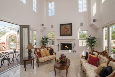 To the left a 2-story Living Room with an elegant fireplace and French doors