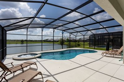 Sunny pool deck with large pool, spa and deck area with lake view