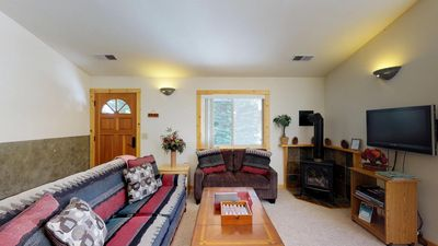 Entrance into Living Area with couches, Fireplace, and TV