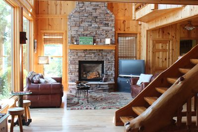 Beautiful lake side living room with stone fire place and two story windows