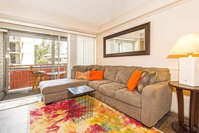 Tan sectional couch on top of a pink and yellow rug
