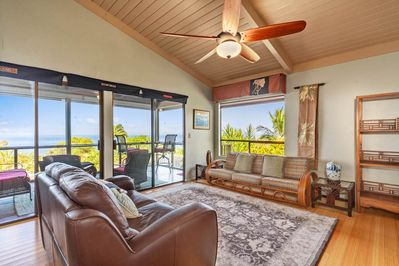 Living room with high wood ceiling, two couches, and lanai