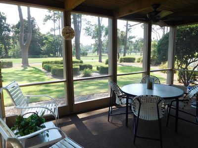 LARGE SCREEN PORCH WITH A CEILING FAN OVERLOOKS THE 9TH TEE HARBOUR TOWN COURSE