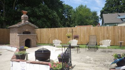 Outdoor patio area with brick wood-fired oven, firepit, grill, and bar.