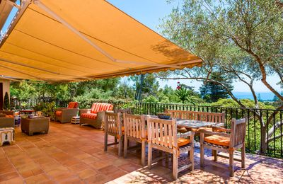 An awning and olive trees shade the terrace, which has spectacular  ocean/island