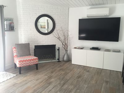 "Modern, clean, living room with AC/Heat, 65"" TV,  DVD, Remote fireplace"