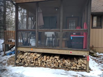 View of screened porch with free firewood for fireplace and firepit