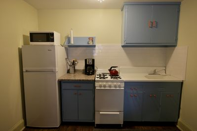 Urban kitchen with gas range, microwave, and efficiency refrigerator.
