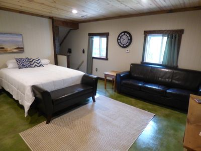 Includes white bedding, leather furniture, concrete flooring, & natural lighting