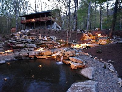 Waterfall and fire pit lit up at night