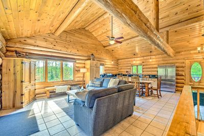 The spacious open-concept layout has exposed wood logs and a rustic vibe.