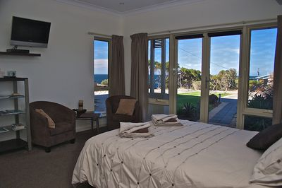 Spacious master bedroom offering sea views with reading corner and tub chairs.