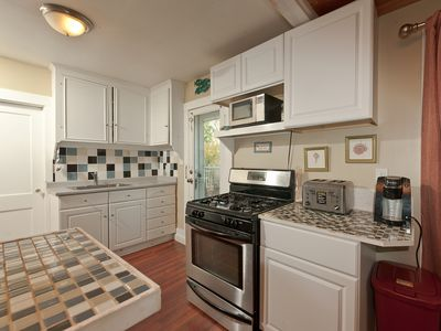 Kitchen with gas range & oven, microwave, toaster, new refrigerator & cookware