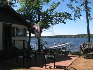 View of dock extending into lake. Patio, grill, fire ring, picnic table, seating