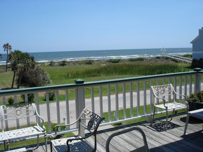 Beach and water view from front porch. Dining tables, chairs and chaise lounges.