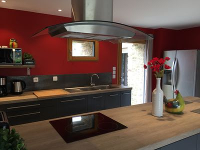 Kitchen equipped with an American refrigerator, an induction hob and central ext