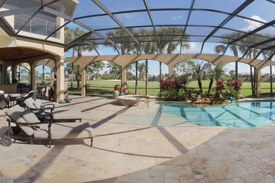 The screened in lanai has a separated grilling station with a wet bar and multiple lounge areas