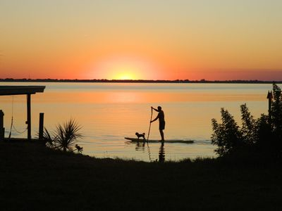 Man and His Best Friend Paddle Boarding at Sunset on the Banana River.