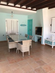 front door with covered patio table for eating el fresco dining and BBQ