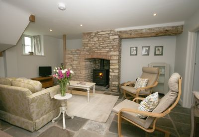 Sitting room with wood-burner and circular stone staircase hidden in the corner.