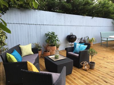 Decking area with bbq, dining table for 12, and a lounging area