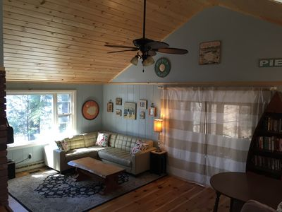 Livingroom with pine vaulted ceiling and skylights facing the kitchen.