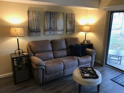 Reclining couch with middle console pull down charging station and cup holders