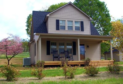 Front of the home with rocking chairs as the plants are starting to bloom