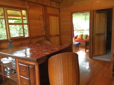 View of kitchen with comfortable hand woven seating for 4 & attached living area