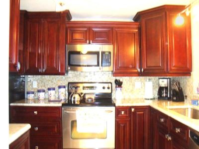 Cherry Kitchen with granite and stainless steel appliances.