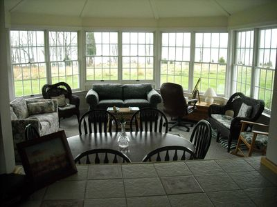 View of the sunroom, lawn, bluff, and bay beyond, from the buffet in the kitchen
