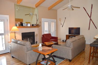 Large open family room with vaulted ceilings, fireplace and wood floors