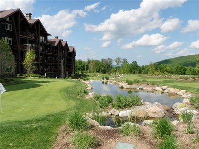 Front view of Grand Cascades Lodge putting green and pond