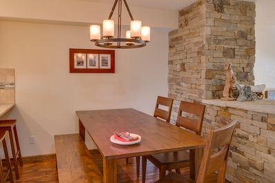 Large dining table is adjacent to well-stocked kitchen with breakfast bar, and there is ample seating for nine