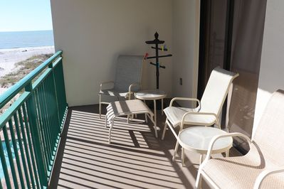 Balcony has 4 chairs, 1 ottoman, and towel holder