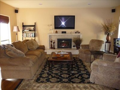 Living room with hardwood floors, gas fireplace, flat screen tv, game table