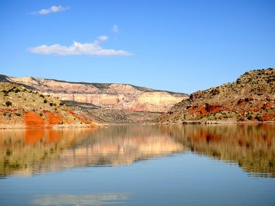 Beautiful Abiquiu Lake, surrounded by purple mountains and red rock formations.