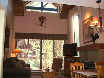 Vaulted Living room with fireplace, looking onto trees and Blackcomb Mountain