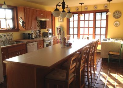 Sunny eat-in kitchen is fully equipped for cooking and dining.