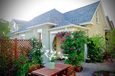 The front of our home, with cottage garden patio dining and spring roses.