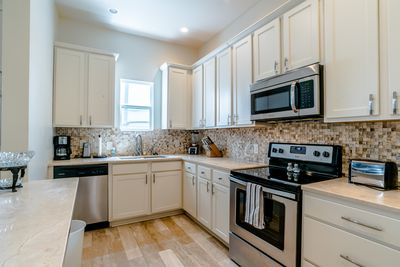 New upscale kitchen equipped for cooking, granite countertops, stainless.