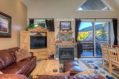 Large open great room with leather sofa, gas fireplace, views and flat screen TV