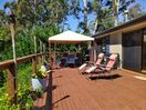 our sundrenched balcony with dining table under the gazebo and 4 sun lounges