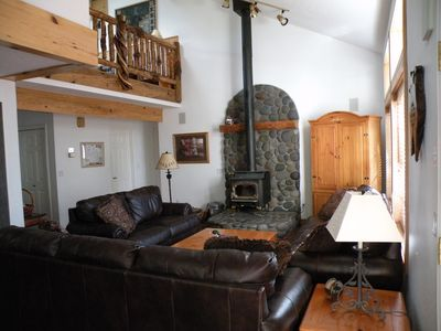 Great Room with view of loft area and cozy wood stove.  Wood provided.