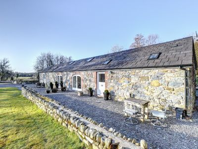 Photo for This beautifully converted barn boasts exposed beams and stonework along with large arched windows c